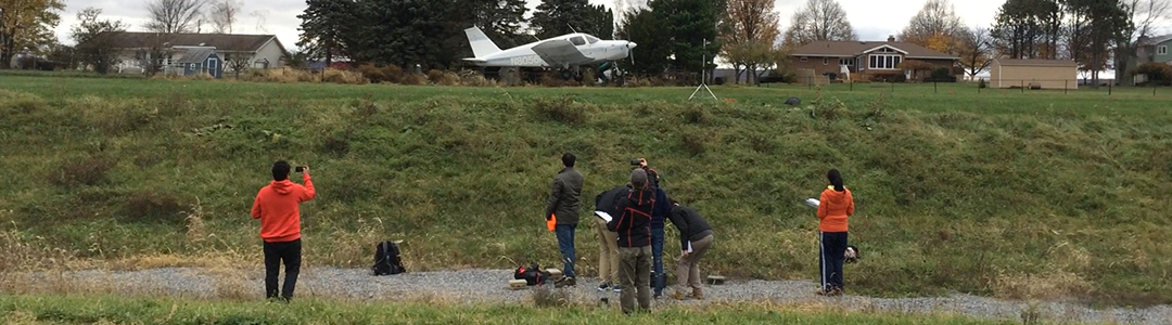 Students take outdoor noise measurements on a small runway.